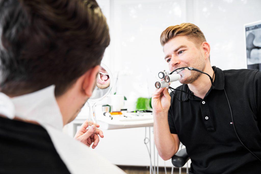 Zahnarztpraxis White Spot Robert Mühlig mit Lupenbrille im Gespräch